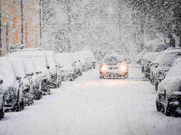Ein Auto fährt am Dienstag durch einen verschneite Straße in München.