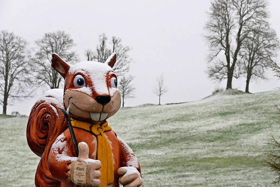 Mit Schnee bedeckt steht am Ostersonntag ein überdimensionales Eichhörnchen vor einer Skischule in Nesselwang (Bayern). (Foto: dpa)