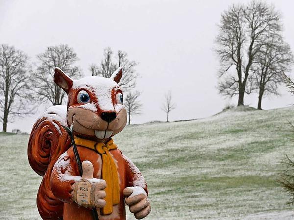 Mit Schnee bedeckt steht am Ostersonntag ein überdimensionales Eichhörnchen vor einer Skischule in Nesselwang (Bayern).