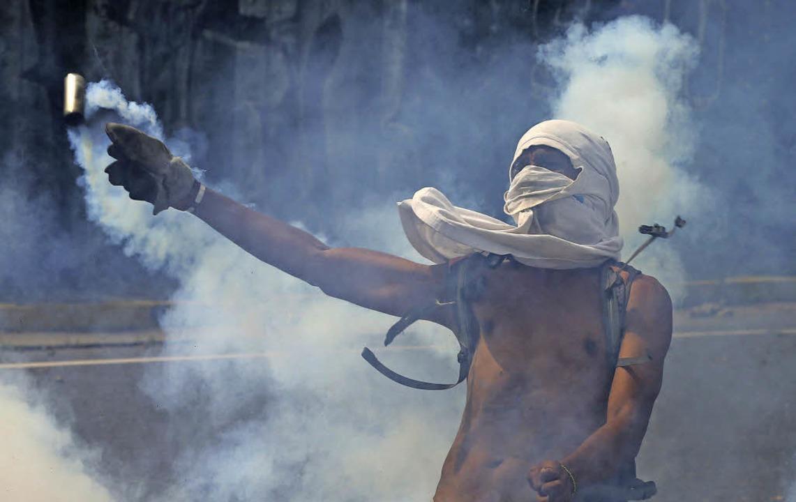 Ein Demonstrant  in Venezuela wirft ei...kartusche zurück in Richtung Polizei.   | Foto: dpa