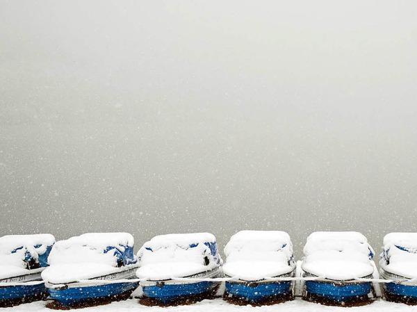 Schnee liegt auf Tretbooten, die am Titisee bei Titisee-Neustadt  liegen.