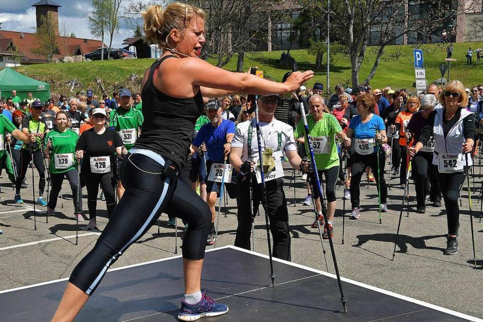Susi Pfitzer, Sportlehrerin und Fitnesstrainerin aus Freiburg, bringt die 600 Nordic Walker in Schluchsee vor dem Start in Schwung. (Foto: Wolfgang Scheu)