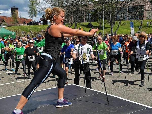 Susi Pfitzer, Sportlehrerin und Fitnesstrainerin aus Freiburg, bringt die 600 Nordic Walker in Schluchsee vor dem Start in Schwung.