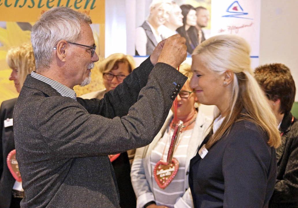 Zur Eröffnung hängt Michael Szymczak v...in Anja Hoffmann ein Lebkuchenherz um.  | Foto: Horst David