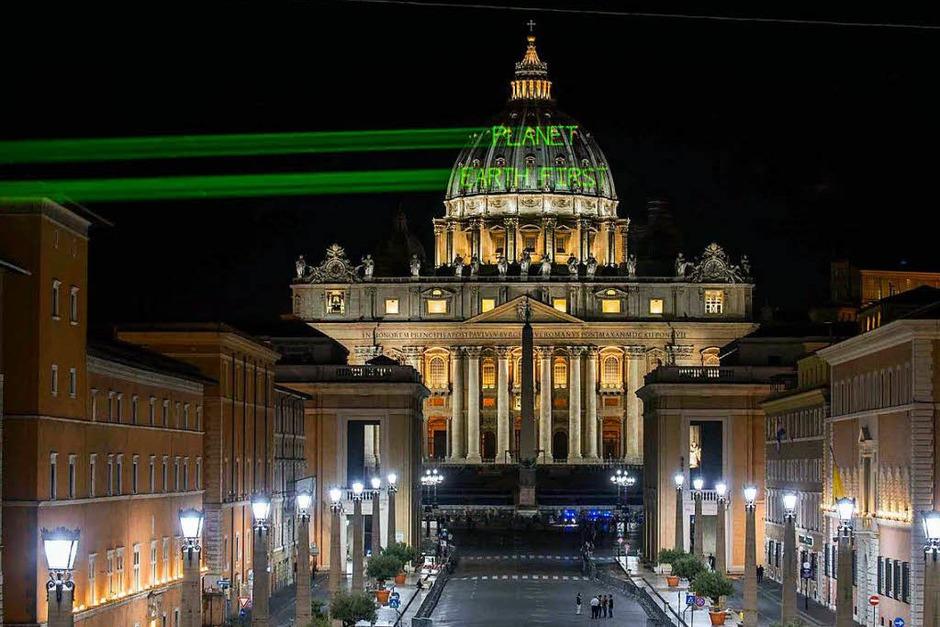 Aktivisten von Greenpeace strahlen die Kuppel des Petersdoms mit der Aufschrift «Planet EarthFirst» an. Am Vorabend des Besuchs von US-Präsidenten Trump beim Papst hat  eine besondere Botschaft an den US-Präsident gerichtet. Dies sei eine Anspielung auf Trumps Motto «America First». (Foto: dpa)