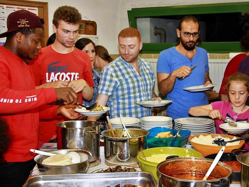 Teti, einer der Köche, serviert einem Syrer das afrikanische Yamsragout.    Foto: Babette Staiger