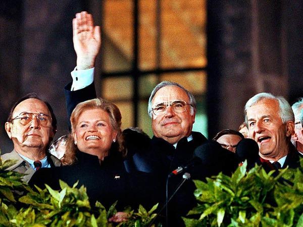 Bei der Berliner Feier am 03.10.1990 winken von der Freitreppe des Reichstagsgebäude (l-r) Bundesaußenminister Hans-Dietrich Genscher (FDP), Hannelore Kohl, Bundeskanzler Helmut Kohl (CDU) und Bundespräsident Richard von Weizsäcker.