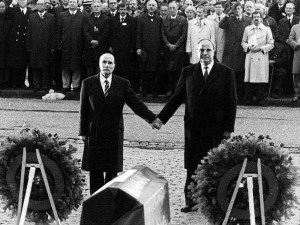 Der französische Staatspräsident Francois Mitterrand (l) und Bundeskanzler Helmut Kohl reichen sich am 22.9.1984 über den Gräbern von Verdun die Hand.