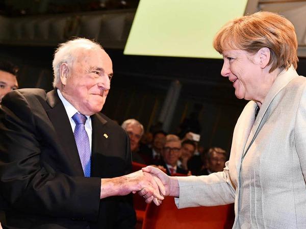 Bundeskanzlerin Angela Merkel (r, CDU) begrüßt am 23.04.2015 in Ludwigshafen (Rheinland-Pfalz) bei einer Feier zum 150-jährigen Bestehen des weltgrößten Chemiekonzerns BASF Ex-Bundeskanzler Helmut Kohl.