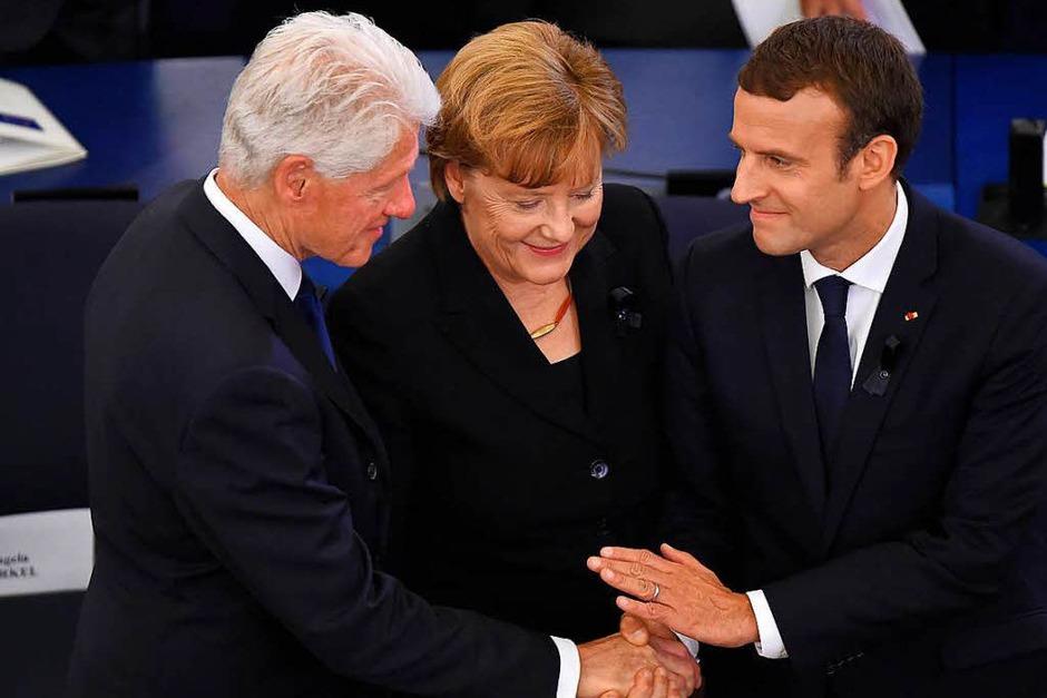 Bundeskanzlerin Angela Merkel und der französische Präsident Emmanuel Macron (r.) zusammen mit dem ehemaligen US-Präsident Bill Clinton. (Foto: AFP)