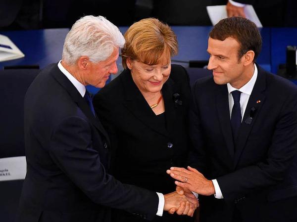 Bundeskanzlerin Angela Merkel und der französische Präsident Emmanuel Macron (r.) zusammen mit dem ehemaligen US-Präsident Bill Clinton.