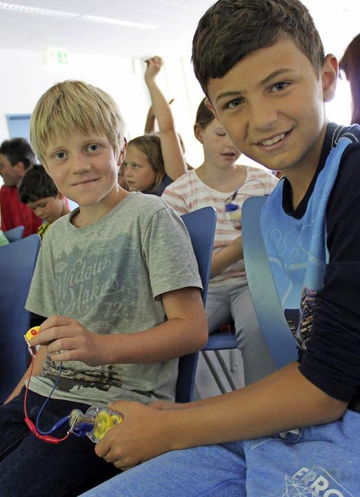 Die Jungs halten einen Mini-Generator,...urbel ein Lämpchen mit Strom versorgt.  | Foto: Bendikt Metzger
