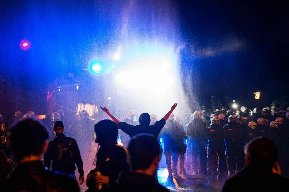 Ein Wasserwerfer spritzt  am Neuen Pferdemarkt in St. Pauli Wasser auf eine Menschenmenge. Hunderte Menschen hielten sich auf der Straße auf und behinderten den Verkehr (Foto: dpa)