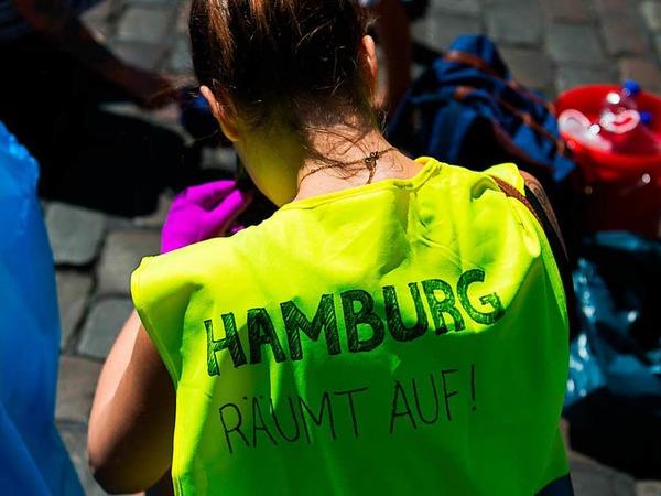 Bewohner versammeln sich am Sonntag in Hamburg vor dem Bahnhof Sternschanze, um das Schanzenviertel aufzuräumen