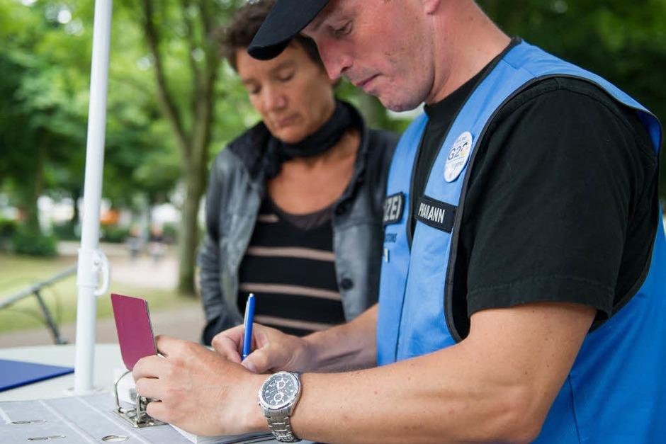 Ein Polizist nimmt am 10.07.2017 in Hamburg bei einem Infomobil der Polizei die Daten einer Frau auf, die während der Krawalle in Hamburg Sachschaden erlitten hat. Bei dem Infomobil können Betroffene Sachschaden melden, der während des G20-Gipfels entstanden ist. (Foto: dpa)