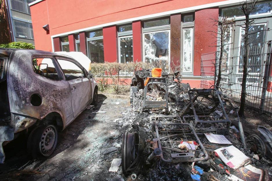Zwei ausgebrannte Fahrzeuge stehen auf dem Hof einer Pflegeeinrichtung für Senioren in Altona (Foto: dpa)