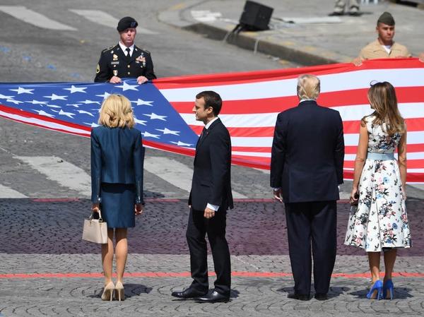 Ehepaar Trump und Ehepaar Macron stehen vor der amerikanischen Nationalflagge