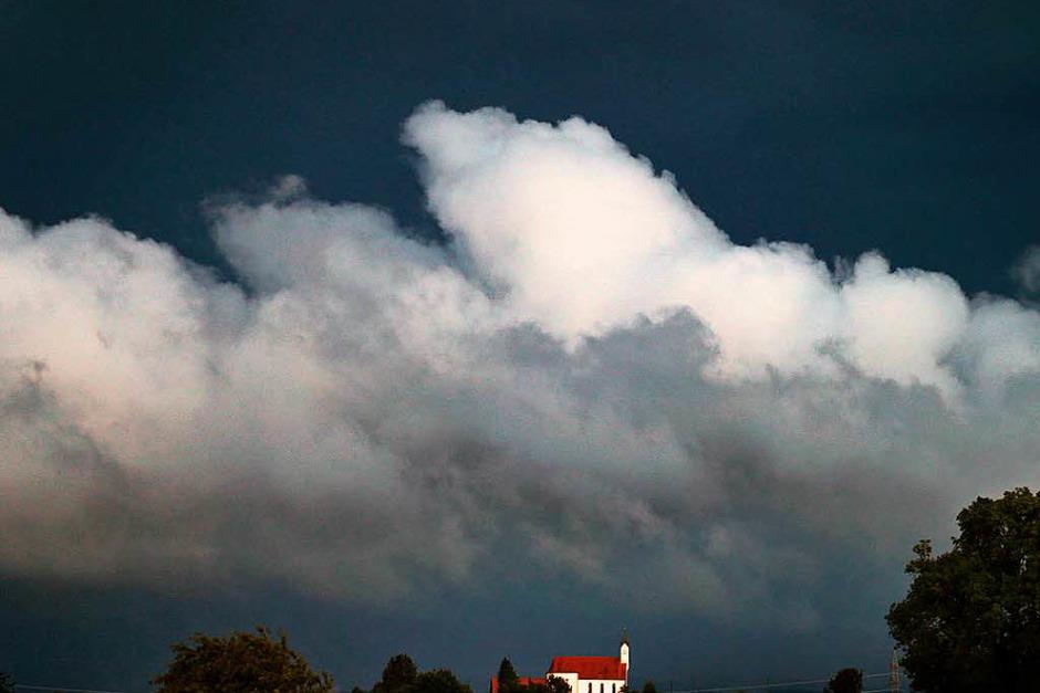 Wolken türmen sich über der Wallfahrtskirche Sankt Alban bei Aitrang in Bayern. (Foto: dpa)