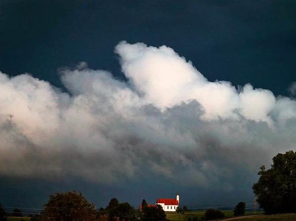 Wolken türmen sich über der Wallfahrtskirche Sankt Alban bei Aitrang in Bayern.