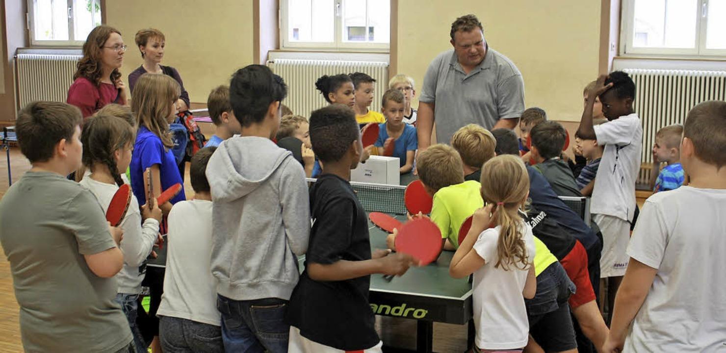 Umringt von Kindern und Jugendlichen: ...itte) vom Tischtennis-Schnuppermobil.     Foto: Werner Schnabl