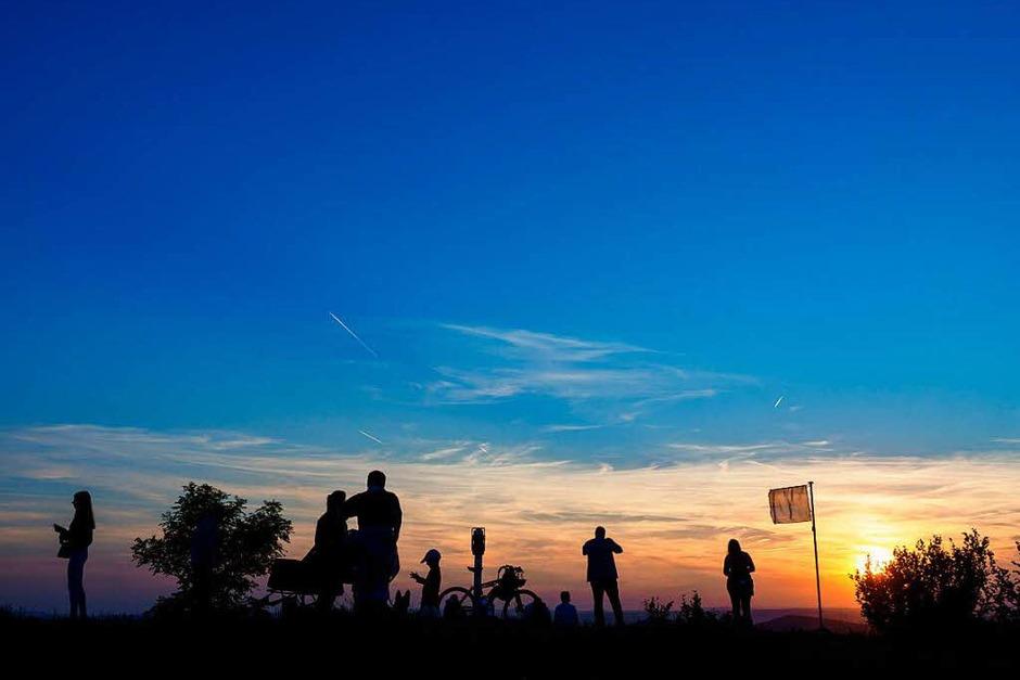 Mehrere Wanderer sind  auf dem Staffelberg bei Bad Staffelstein (Bayern) während des Sonnenuntergangs zu sehen. Viele Schaulustige warteten auf dem Staffelberg auf den Aufgang des Mondes, um die partielle Mondfinsternis zu sehen. (Foto: dpa)