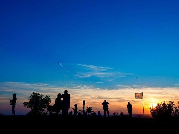 Mehrere Wanderer sind  auf dem Staffelberg bei Bad Staffelstein (Bayern) während des Sonnenuntergangs zu sehen. Viele Schaulustige warteten auf dem Staffelberg auf den Aufgang des Mondes, um die partielle Mondfinsternis zu sehen.