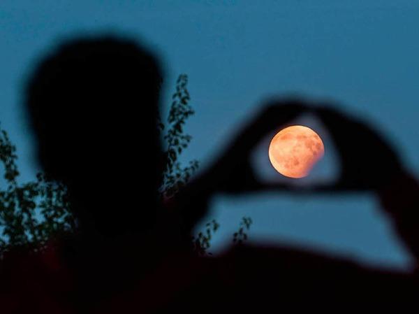 Ein Mann visiert in Frankfurt am Main (Hessen) mit seinen Händen die partielle Mondfinsternis an, die er am Bornheimer Hang verfolgt.