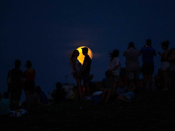 Menschen betrachten  im Cerro Del Tio Pio Park inMadrid (Spanien) die partielle Mondfinsternis .