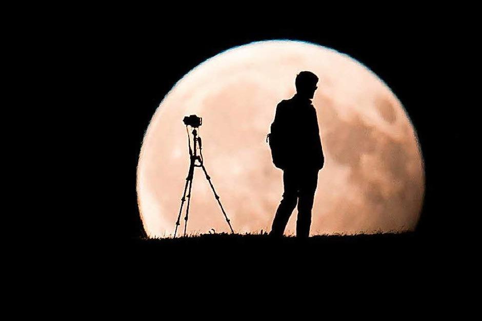 Ein Mann fotografiert in München den Mond. (Foto: dpa)