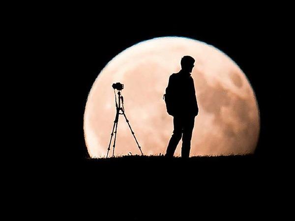 Ein Mann fotografiert in München den Mond.