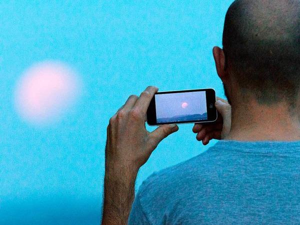 Ein Mann fotografiert  in Bielefeld (Nordrhein-Westfalen) bei einer partiellen Mondfinsternis den Mond mit seinem Handy.