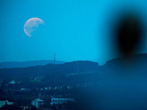 Ein Mann beobachtet in Bielefeld (Nordrhein-Westfalen) die partielle Mondfinsternis.