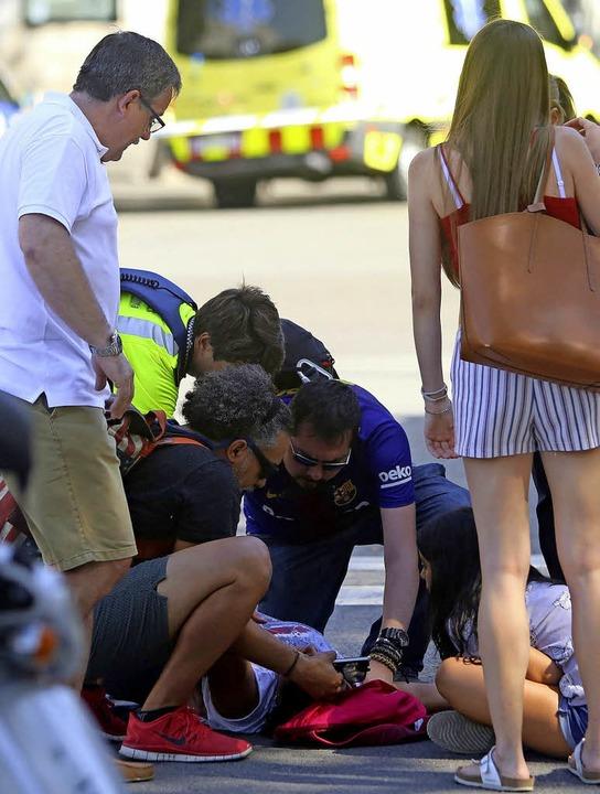 Helfer kümmern sich nach dem Anschlag  um eine Verletzte.    | Foto: dpa