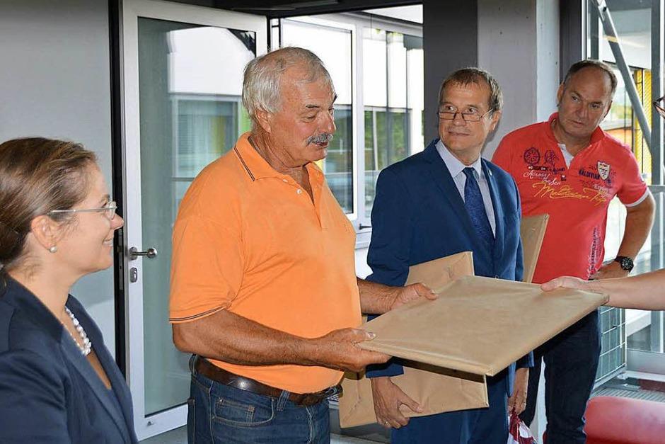 Stéphanie Niville (rechts) von den Marinettes hatte auch für Daniel Billiaux (Zweiter links), Vorsitzender des Comités Jumelage in Fécamp, ein Präsent dabei. (Foto: Horatio Gollin)