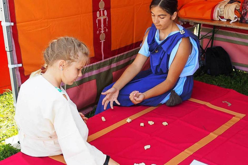 Alina Ackermann (rechts) zeigt den Besuchern, wie man das Knöchelspiel spielt. (Foto: Boris Burkhardt)