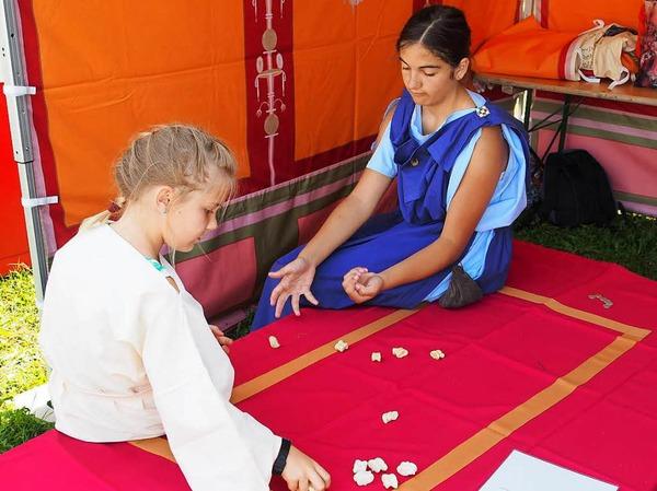 Alina Ackermann (rechts) zeigt den Besuchern, wie man das Knöchelspiel spielt.