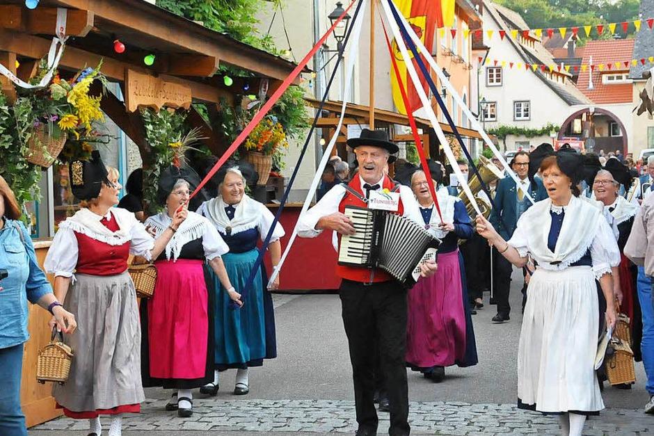 Zur Eröffnung zieht die Trachtengruppe mit dem Musikverein auf dem Festgelände im alten Merdinger Ortskern ein. (Foto: Sebastian Ehret)