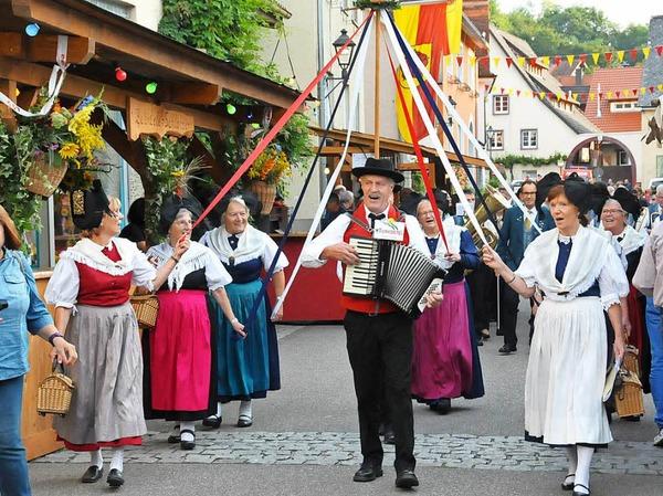 Zur Eröffnung zieht die Trachtengruppe mit dem Musikverein auf dem Festgelände im alten Merdinger Ortskern ein.
