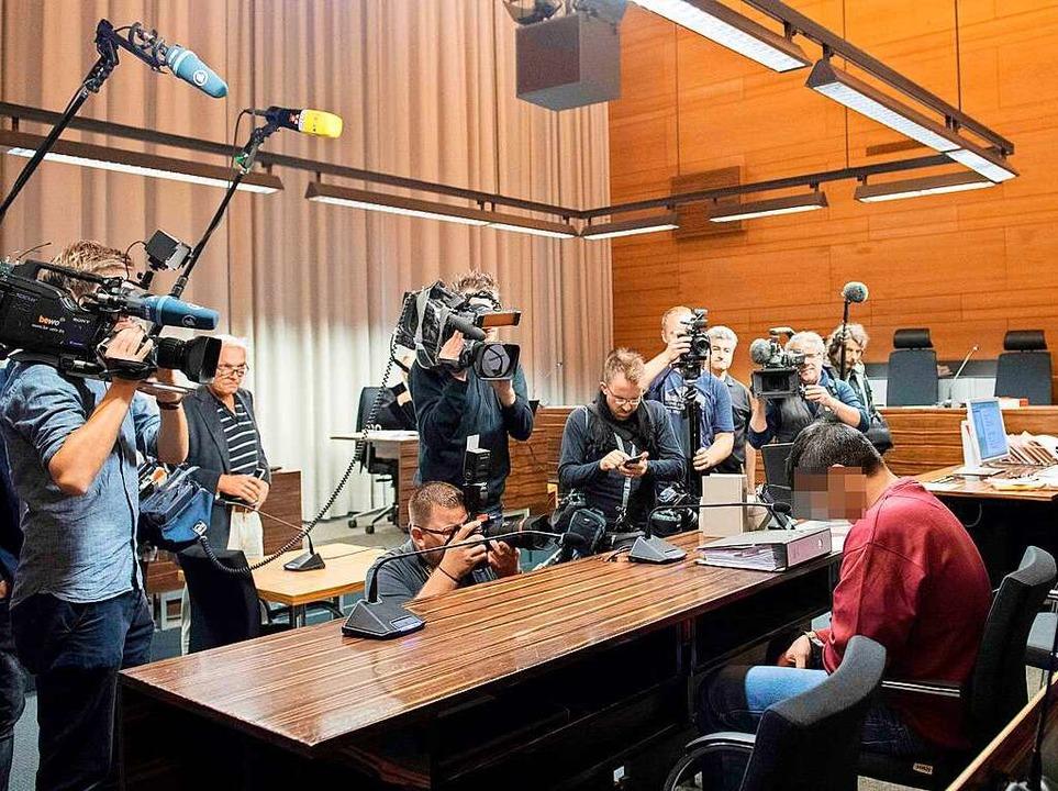 Kamerateams und Fotografen und der Ang...ussein K. am Dienstag im Gerichtssaal.  | Foto: AFP