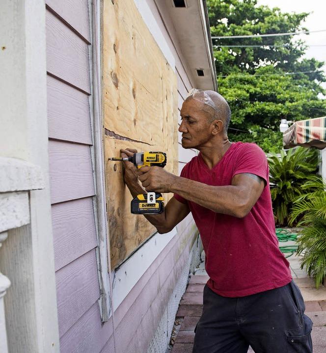 Ein Mann sichert die Fenster seines Hauses mit Holzplatten vor dem Sturm.  | Foto: AFP