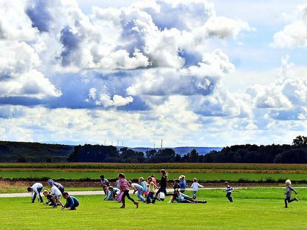Süßer Spaß: Ein Modellflieger hat Bonbons vom Himmel regnen lassen, die Kinder stürzen sich vergnüglich drauf.