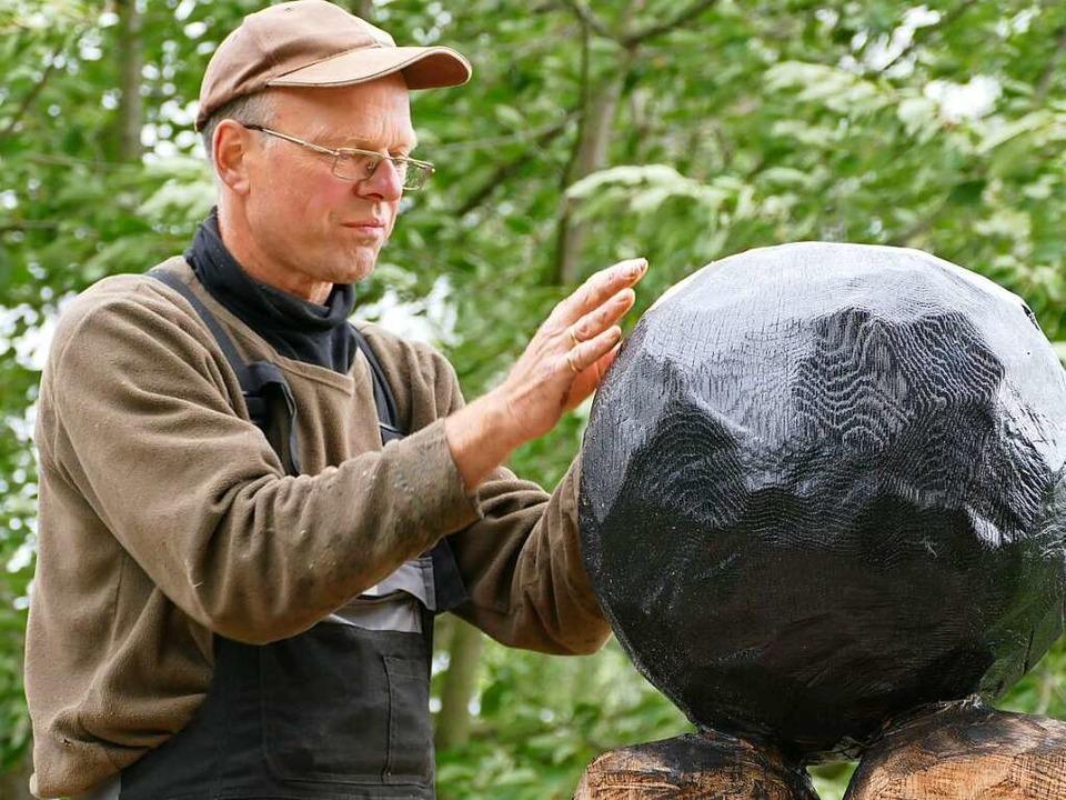 Roger Löcherbach beklebt einen Teil seiner Skulptur mit Blattgold.  | Foto: Lena Marie Jörger