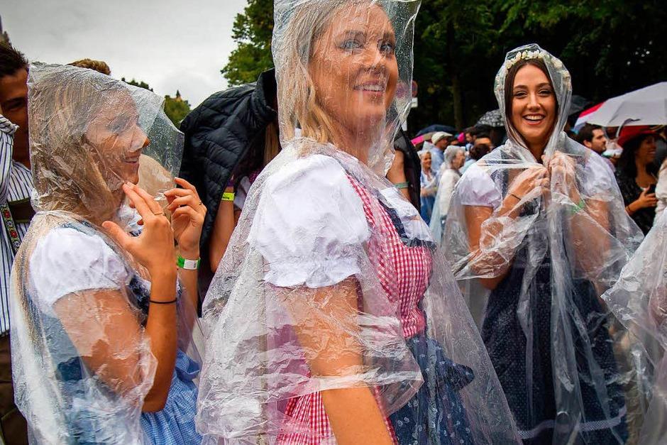 Zehntausende Menschen kamen bereits seit den frühen Morgenstunden trotz Regens auf die Theresienwiese. Dort waren durchsichtige Capes und Regenschirme ein beliebtes Utensil für die sonst meist in bunte Tracht gehüllten Besucher. (Foto: dpa)