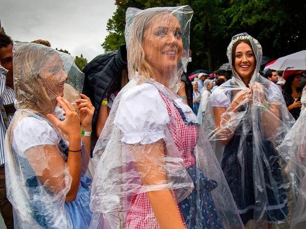Zehntausende Menschen kamen bereits seit den frühen Morgenstunden trotz Regens auf die Theresienwiese. Dort waren durchsichtige Capes und Regenschirme ein beliebtes Utensil für die sonst meist in bunte Tracht gehüllten Besucher.