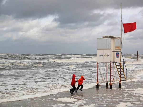 Kinder  auf dem Strand von Wangerooge (Niedersachsen) laufen bei stürmischen Wind vor den Wellen davon.