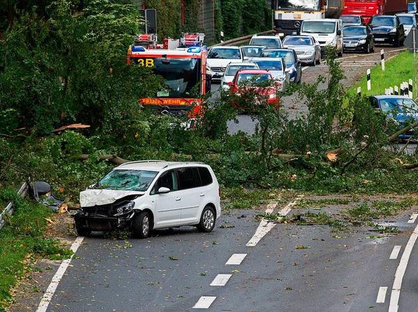 """Ein beschädigtes Auto steht  auf dem Messeschnellweg bei Hannover, nachdem ein Baum auf die Straße gekippt ist. Durch Sturmtief """"Xavier"""" kommt es im Schienen und Straßenverkehr zu Einschränkungen..."""