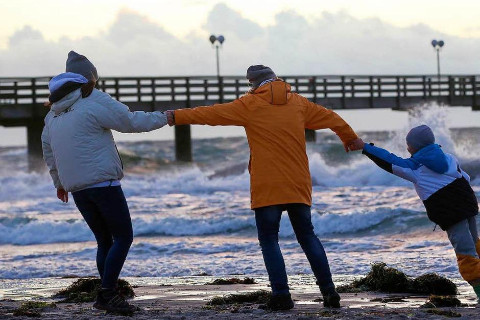 Spaziergänger halten sich bei Sturm an der Ostsee am Strand von Wustrow (Mecklenburg-Vorpommern) gegenseitig fest. (Foto: dpa)