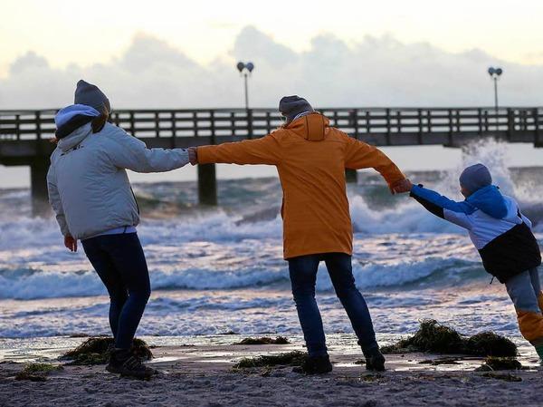 Spaziergänger halten sich bei Sturm an der Ostsee am Strand von Wustrow (Mecklenburg-Vorpommern) gegenseitig fest.