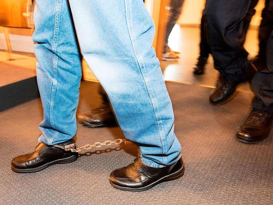 In Fußfesseln wird der Angeklagte Huss...ssaal im Landgericht Freiburg geführt.  | Foto: dpa