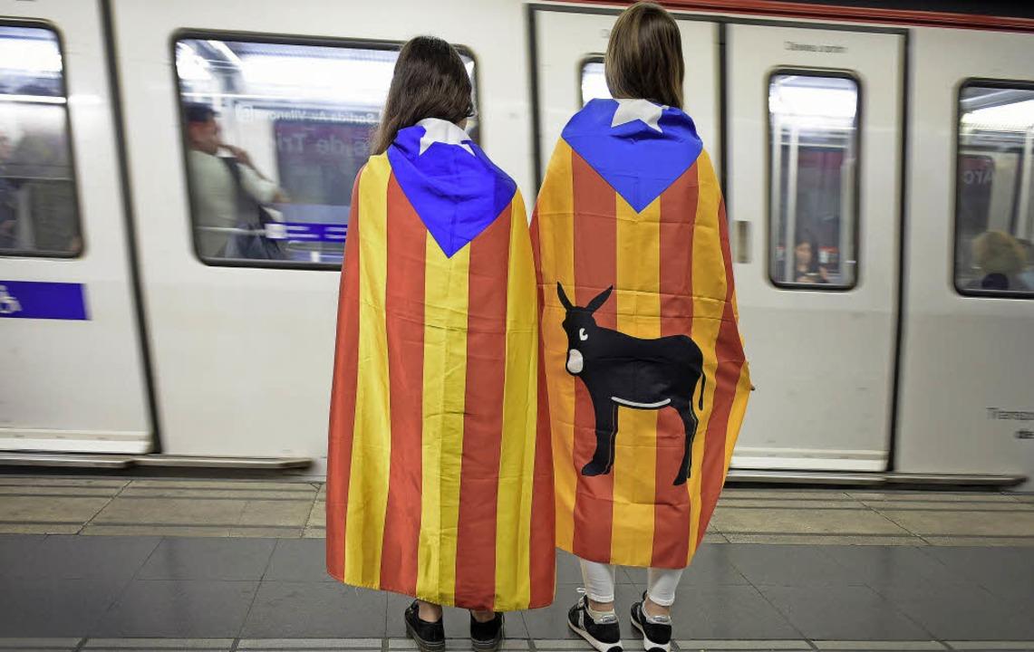 Die katalanischen Farben um die Schult...Frauen an einem Bahnsteig in Barcelona    Foto: dpa